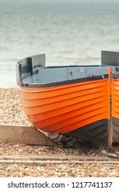 Small orange and black fishing boat on a shingle beach