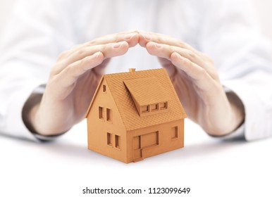 Small orange house protected by hands