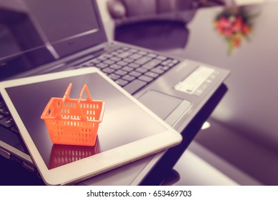 Small orange plastic basket on a white smart tablet, a laptop and office desk. Concept of shopping that consumers can shop or buy everything online from home or office worldwide by using the internet.