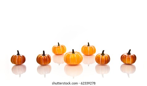 Small orange pumpkins in rows on a white background.