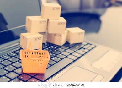 Small orange shopping basket on a laptop keyboard with boxes behind. Concept of shopping that consumers or customers can buy products or services online directly from sellers on the internet worldwide