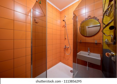 Small orange tile bathroom with Shower cabin and sink