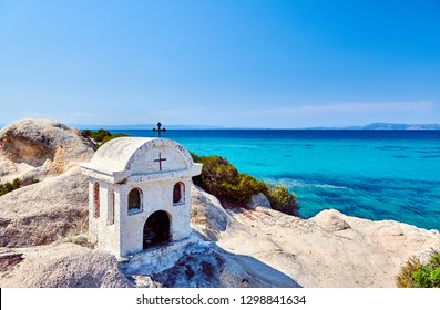 Small orthodox chapel and beautiful rocky coast and turquoise sea water landscape. Kavourotripes beach, Sithonia, Greece