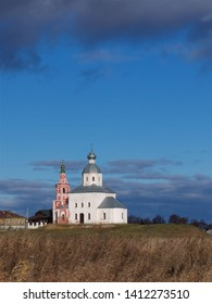 a small Orthodox church on a hill against a blue sky with thunderstorm clouds in the fall, Church of Elijah the Prophet Suzdal Golden Ring of Russia