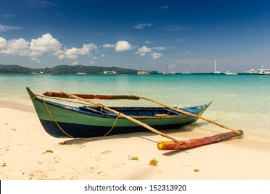 A small outrigger style Banca boat rests on a tropical beach