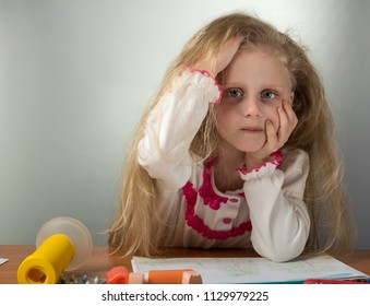Small painful child sitting at table, near inhaler with child's mask, on grey