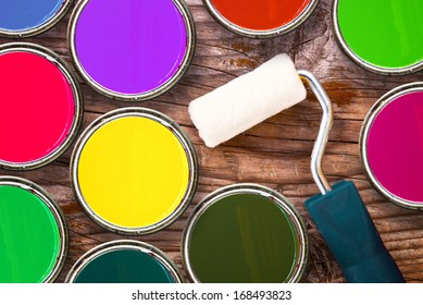Small paint roller and color tin cans on old wood background. Redecoration and renovation concept, top view