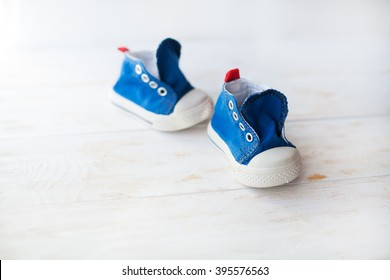 A small pair of blue baby sneakers on a wood floor
