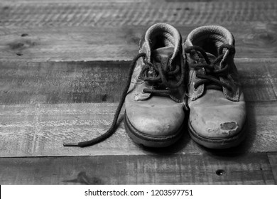 A small pair of children shoes on a old table . Image is in black and white.Rustic looking floor and worn small workbooks