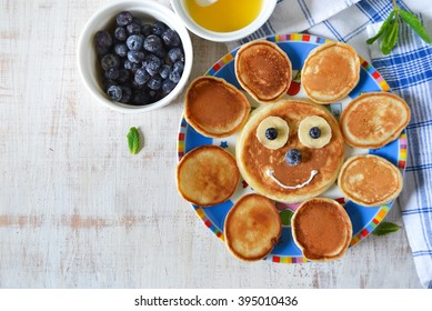 small pancakes with blueberries and bananas for children, breakfast for children