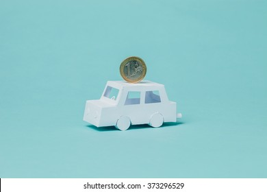 Small paper car with an euro coin. Conceptual image about fuel efficiency, savings and transportation.