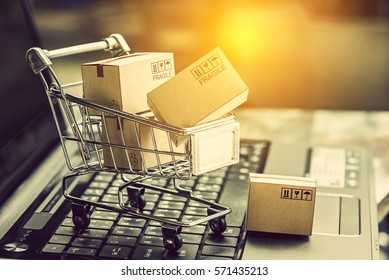Small paper cartons or boxes in shopping cart with one falls outside on a laptop keyboard. Concept about online shopping that everybody can buy or purchase everything easily at hand just a few clicks.