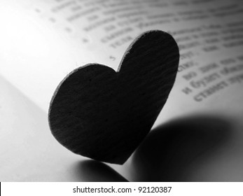 Small paper heart on a book. Black and white style.