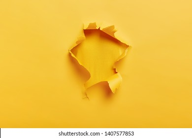 Small paper hole with torn sides over yellow background for your text, print or promotional content. Through paper. Ripped hole. No people. Accurate shot. Advertising and breakthrough concept