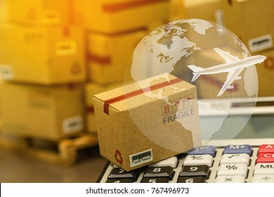 small papers boxes and calculator with a plane flies above world map. business concept of transportation, logistics, global shipping, international freight, overseas trade, regional, go to worldwide .