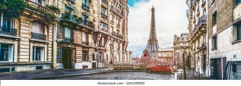 small paris street with view on the famous paris eiffel tower on a cloudy rainy day with some sunshine - wide horizontal panorama