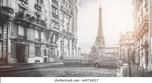 small paris street with view on the famous paris eifel tower on a cloudy rainy day with some sunshine