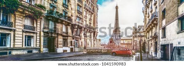 kleine Parisstraße mit Blick auf den berühmten Paris-Eiffelturm an bewölktem Regentag mit Sonnenschein - breites horizontales Panorama