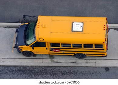"A small parked (van based) yellow school bus from overhead.  Side 'STOP' sign, front safety arm, and room ""EMERGENCY EXIT"" visible."
