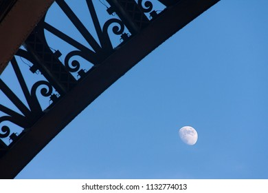 small part of an eiffel tower arch and the moon