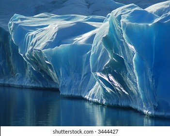 A small part of the sun-reflecting blue front of a larger iceberg. The calm water reflects the beautiful blue ice. Picture was taken during a 3-month Antarctic research expedition near the Peninsula.