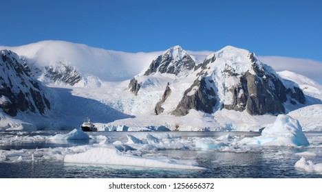 A small passenger vessel stands between icebergs with a spectacular  view of the mountains of Antarctica.