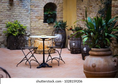 Small patio with tables and chairs. Italy