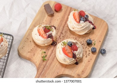 Small pavlova cakes with fresh raspberries and blueberries.