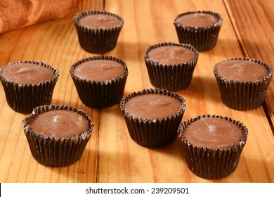 Small peanut butter cups on a rustic wooden table
