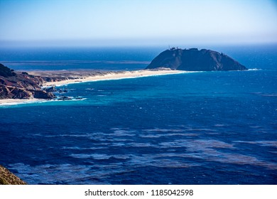 Small peninsula with wild beach juts into deep blue ocean on beautiful scenic coastline