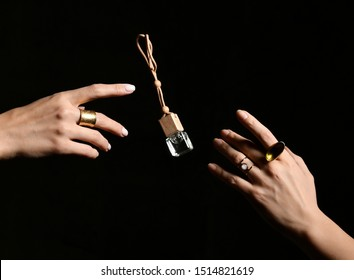 Small perfume bottle is flying from one pretty woman hand with stylish signet rings to another on black background