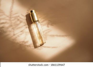 Small perfume bottle on warm pastel and golden colors table. Commercial, brand packaging mockup. Copy space. Refillable travel size. Product photography - Shutterstock ID 1861139647