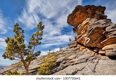 Small person in beautiful rocky mountains of Karkaraly surrounded by forest of national park in Central Kazakhstan