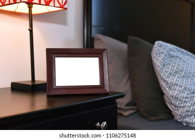 Small personal photo frame to put own memories with copy space. Interior bedroom with nightstand and lamp.