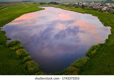 A small picturesque lake among green fields with reflection in it of beautiful clouds of the sunset sky. Aerial view