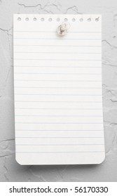 A small piece of blue lined note pad paper thumbtacked to a white textured wall