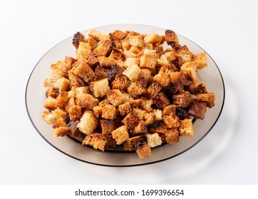 Small pieces of bread fried in oil lying on a transparent brown plate on a light background. Fried crackers.