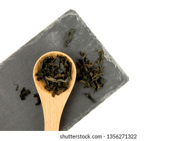 Small pieces of dried Wakame (Undaria pinnatifida), edible seaweed, ingredient to different foods in wooden spoon isolated on white, studio shot.