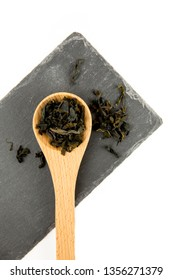 Small pieces of dried Wakame (Undaria pinnatifida), edible seaweed, ingredient to different foods in wooden spoon on black stone cutting board isolated on white, studio shot.