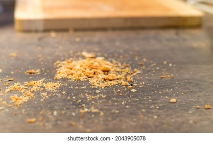 A small pile of breadcrumbs on the kitchen counter