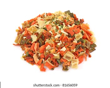 A small pile of dehydrated vegetables used for seasoning on a white background.
