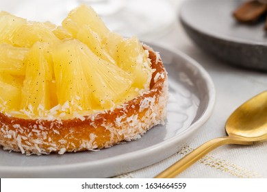Small pineapple tart or tartlet with glazed pineapple fruit pieces and grated coconut by a golden spoon, over a white and gold table cloth.