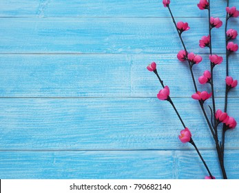 Small pink blossom flowers with brown branch on blue wood background with copy space for wedding or valentine's day greeting card. Flat lay.