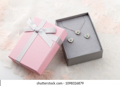 Small pink and gray jewelry gift box with bow on lace background. Pastel color paper present box for jewelry set - necklace and earrings