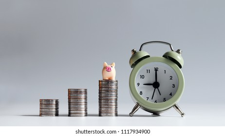 The small pink pig on top of pile of coins with an alarm clock.