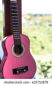 Small pink ukulele guitar on a tropical background. Music instrument.