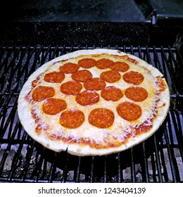 small pizza with pepperoni and cheese on a outdoor gas grill grate charcoal below cooking on a pizza stone