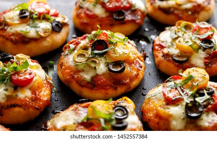 Small pizzas with the addition of cherry tomatoes, olives, mozzarella cheese and fresh basil on a black background, close-up.