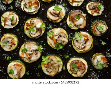 Small pizzas with zucchini with the addition of brown mushrooms, mushroom chanterelles, mozzarella cheese and herbs on a black background, top view, close up. Vegetarian food
