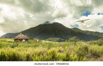 Small plane flying over huts in remote tropical location